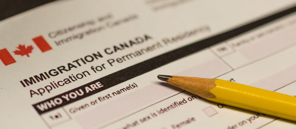 Close-up of the immigration application paperwork for Canada with a pencil laying on top. Image is in full colour