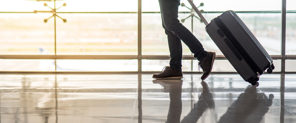 Close up of an individuals legs walking a luggage bag at an airport. Image is in full colour.