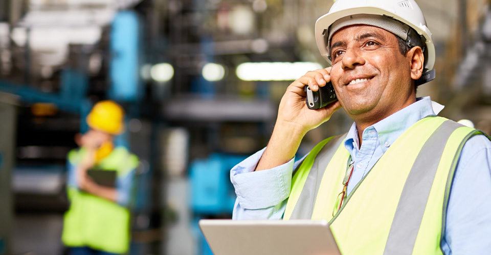 Employee making a work related phone call wearing a yellow safety vest and holding a clipboard. Image is in full colour.